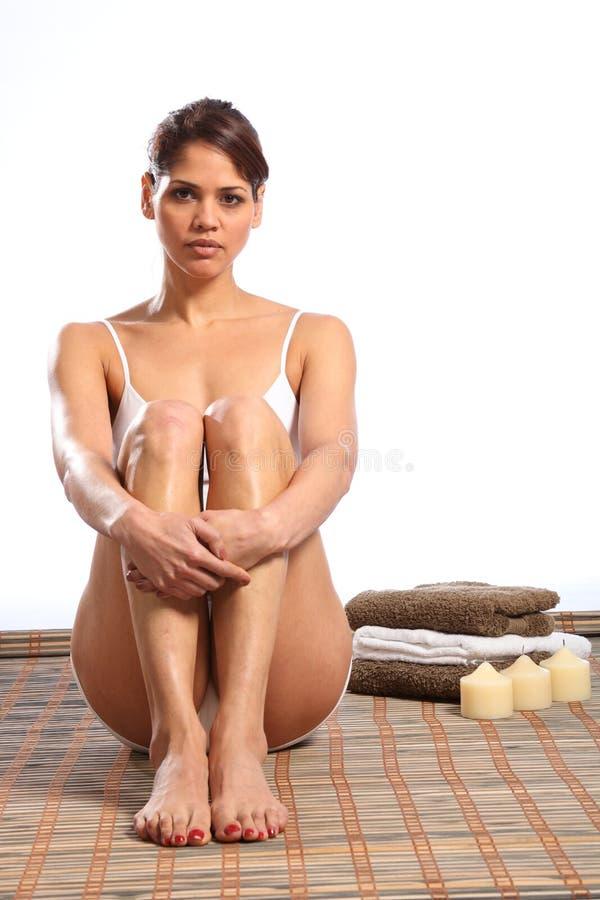 Beau femme dans les sous-vêtements blancs se reposant sur le couvre-tapis image stock