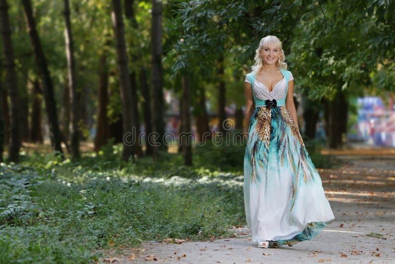 Beau femme de sourire dans la longue robe sur la nature images stock
