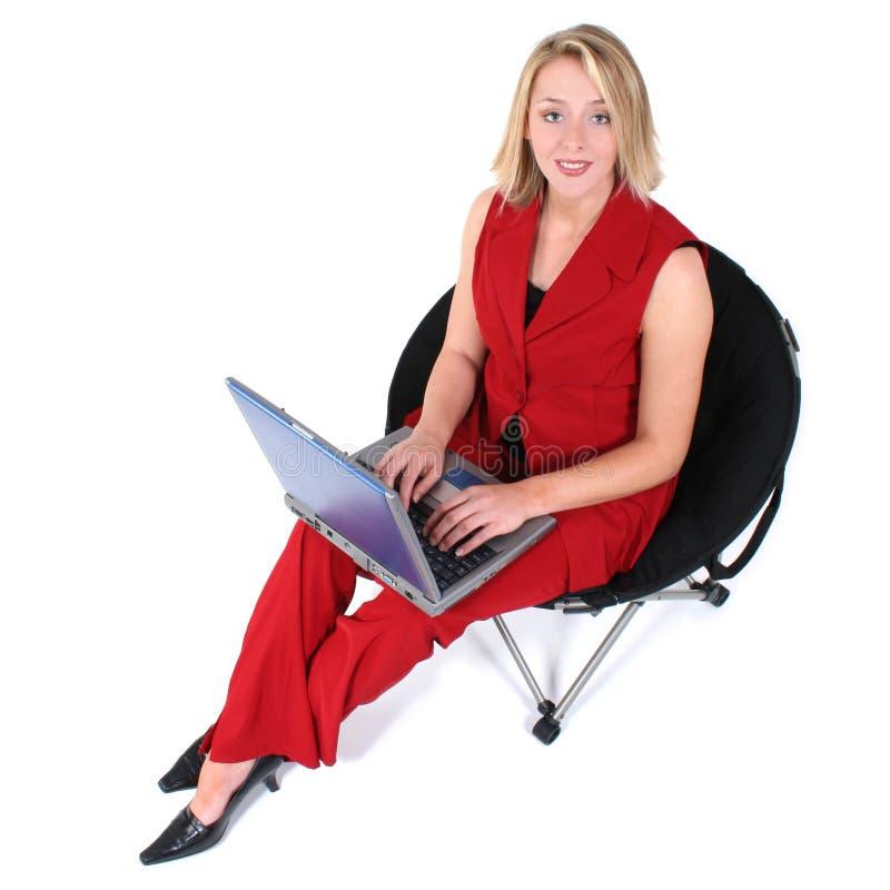 Beau femme en rouge avec l'ordinateur portatif dans la présidence noire photographie stock