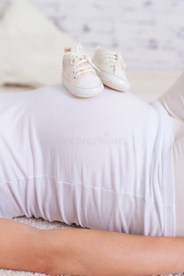 Beau femme enceinte avec des chaussures de chéri sur le ventre photos libres de droits