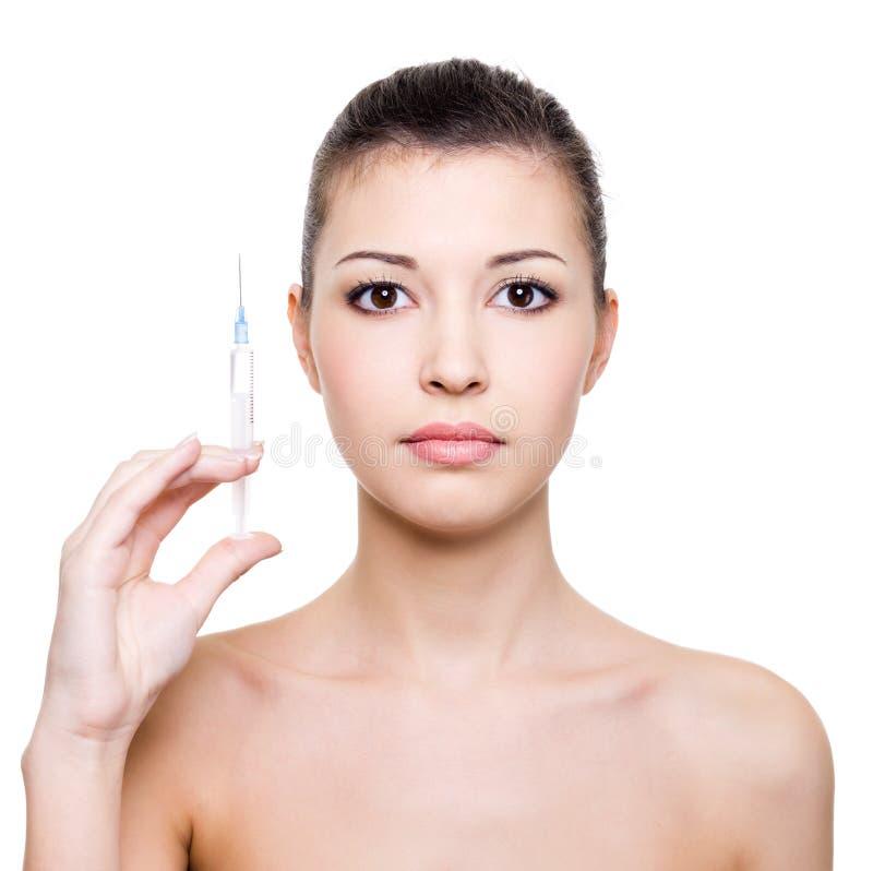 Beau femme retenant la seringue médicale photographie stock