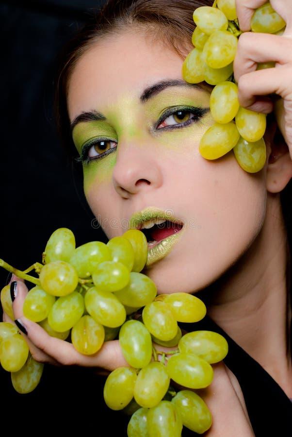 Beau femme retenant le plan rapproché vert de raisins image stock