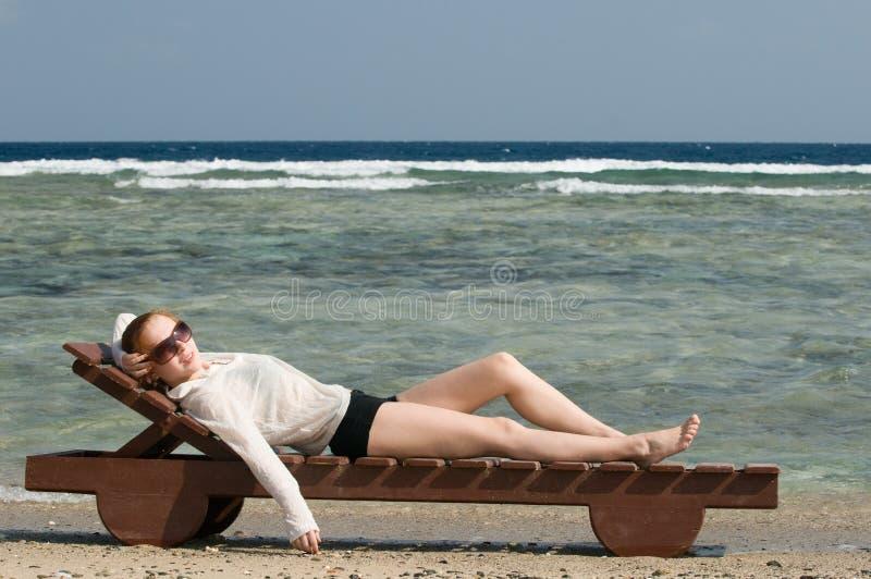 Beau femme rouge détendant près image stock