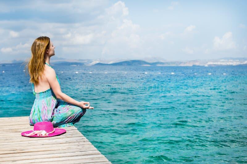 Beau femme s'asseyant à la plage photo stock