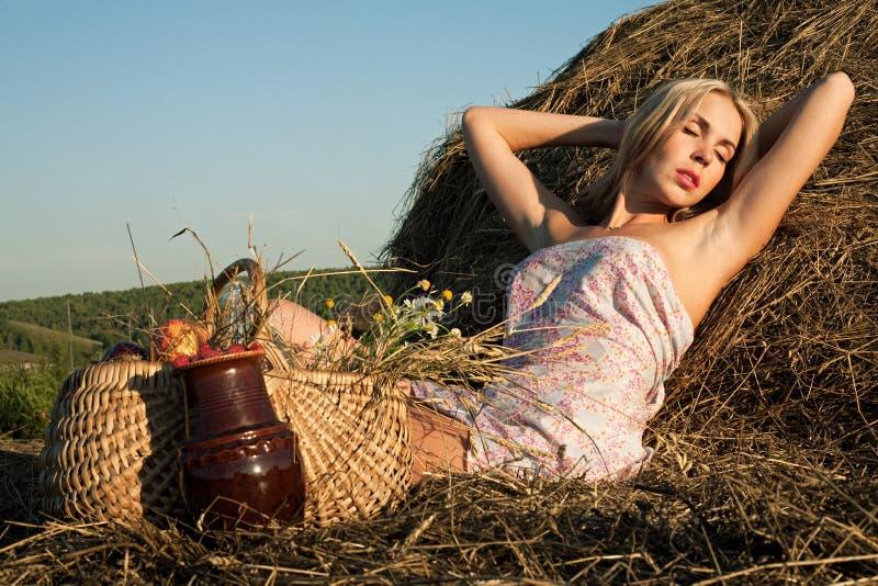 Beau femme s'asseyant sur le foin image stock