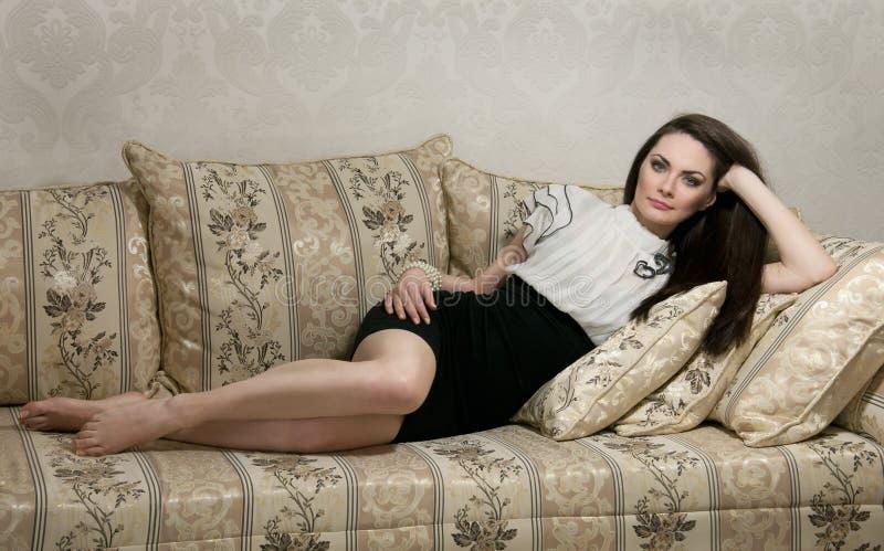 Beau femme se trouvant sur le sofa photos stock