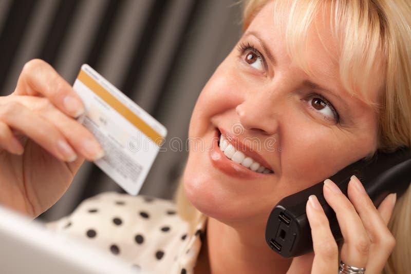 Beau femme sur la fixation de téléphone par la carte de crédit images stock