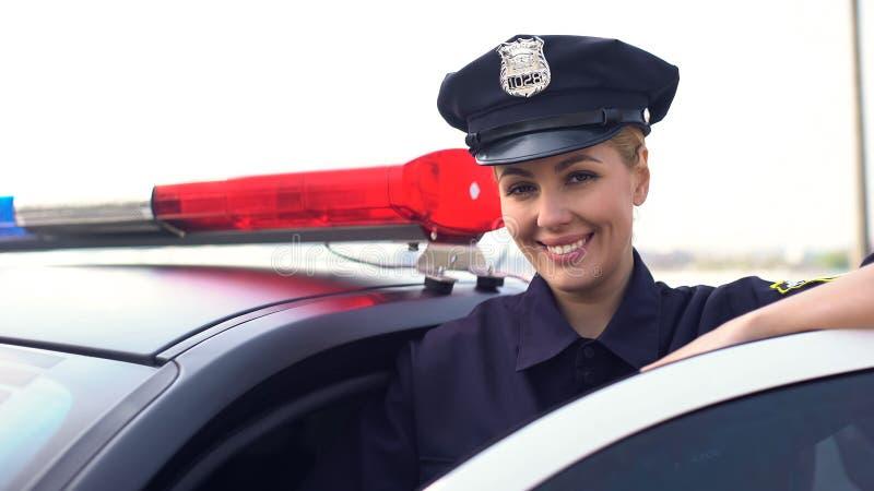 Beau flic de dame dans le chapeau de service souriant à la caméra, ville protectrice de femme images stock