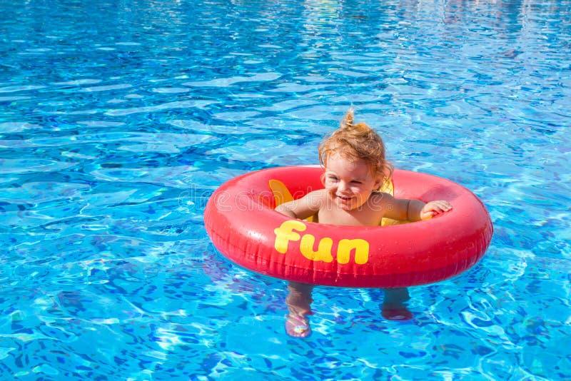Beau flotteur de beignet de petit morceau de petite fille dans la piscine image libre de droits