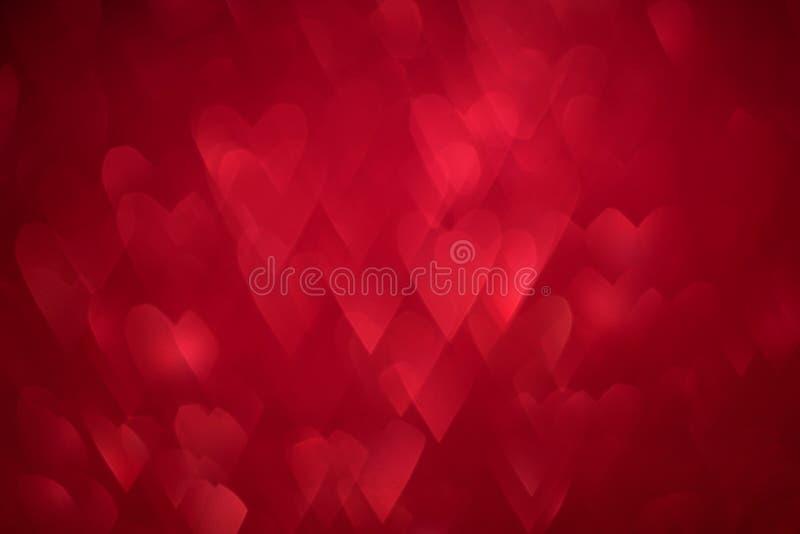 Beau fond de vacances brillantes rouges de scintillement avec des coeurs de forme de bokeh Projectile de studio Carte de voeux de image stock