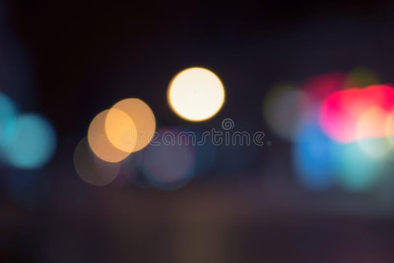 Beau fond defocused de lumières sur l'obscurité photo stock