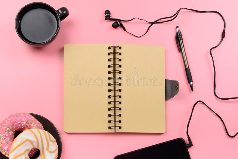 Beau fond Un carnet des ressorts se repose sur un fond rose Autour du bloc-notes il y a des butées toriques de cafés et images stock