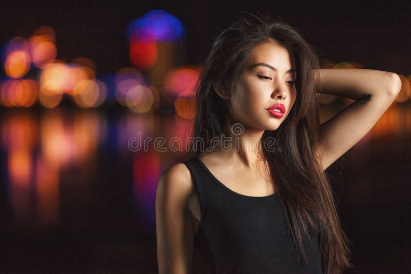 Beau fumage de jeune dame Ville de nuit derrière image stock