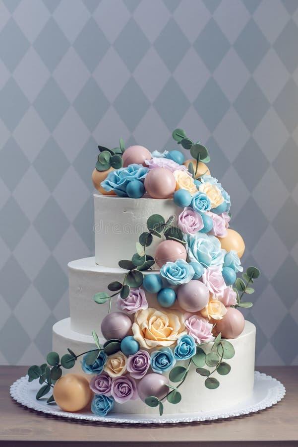Beau gâteau de mariage blanc trois-à gradins décoré des roses colorées de fleurs Concept des desserts élégants de vacances image libre de droits