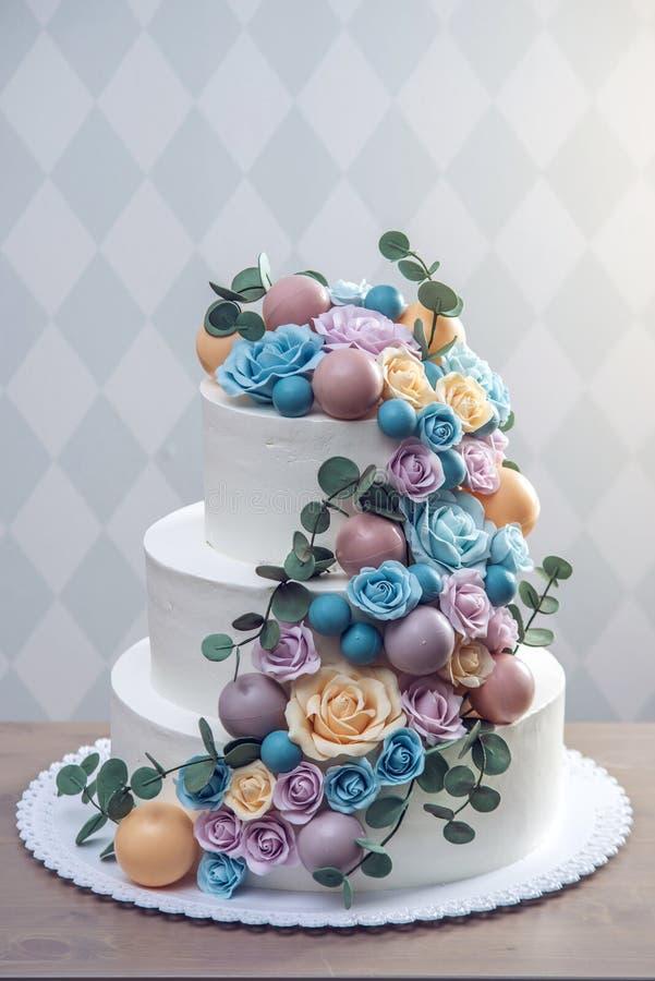 Beau gâteau de mariage blanc trois-à gradins décoré des roses colorées de fleurs Concept des desserts élégants de vacances photos libres de droits