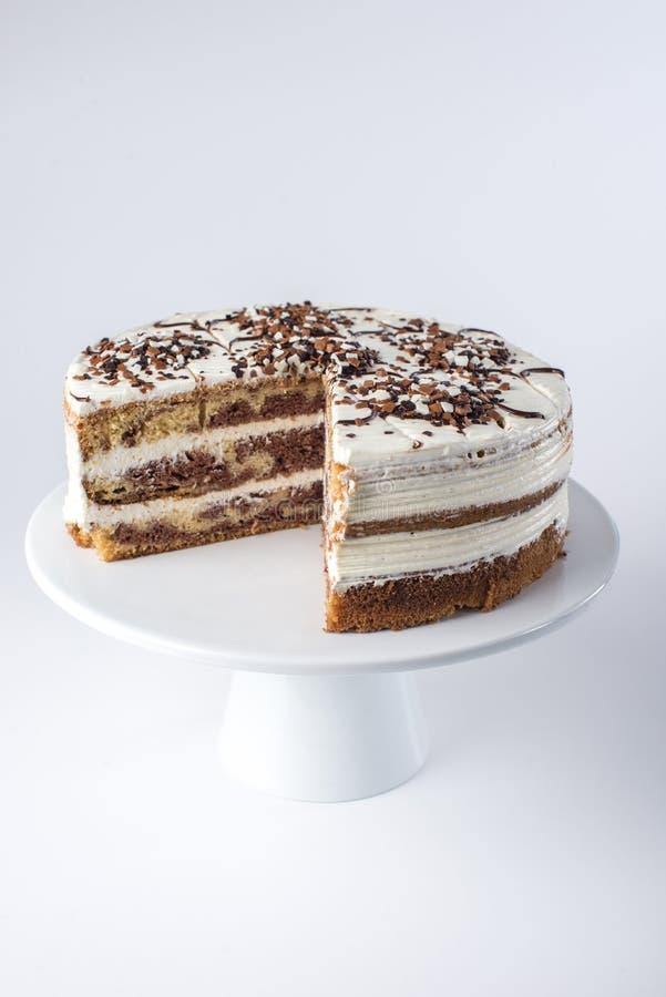 Beau gâteau mousseline posé fait maison d'isolement avec de la crème blanche dans le style rustique avec le morceau coupé photos stock
