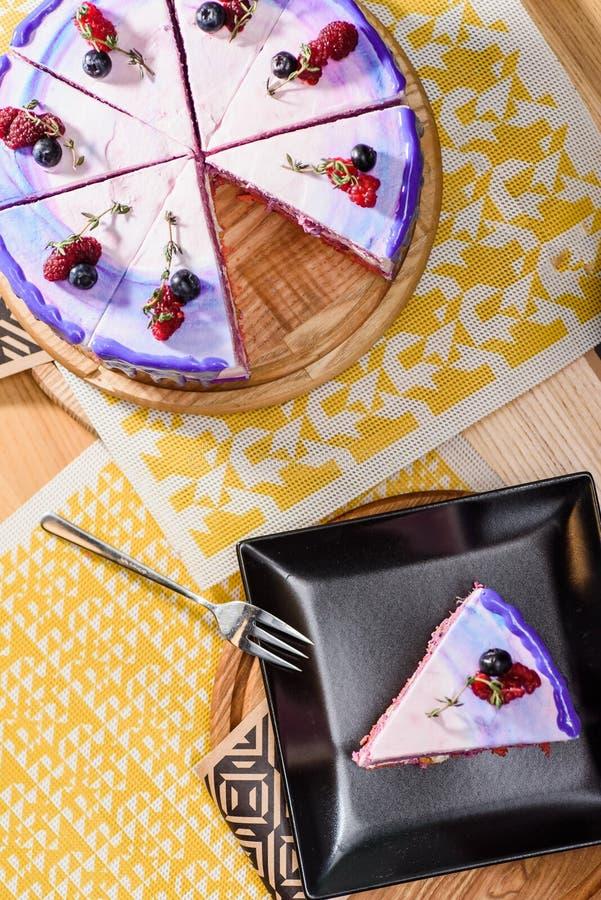 Beau gâteau posé de baie avec une couche pourpre, blanche et rose, décorée des framboises et des myrtilles sur le dessus photos libres de droits