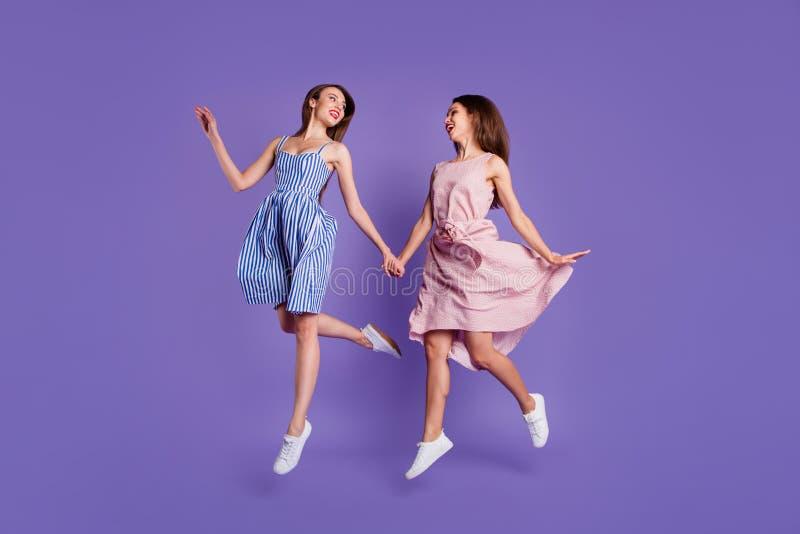 Beau génial de taille du corps de personnes intégrales de la photo deux elle ses modèles que les dames tiennent des mains sautent photo libre de droits