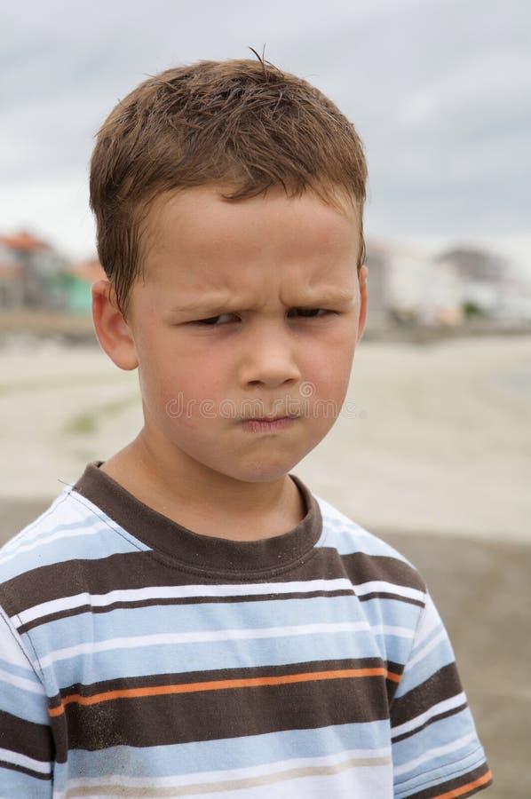 Beau garçon avec le visage fâché photo libre de droits