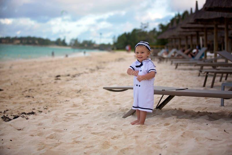 Beau garçon d'enfant en bas âge, habillé en tant que marin, jouant sur la plage sur le coucher du soleil, appréciant des vacances photographie stock