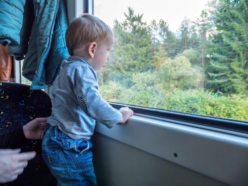 Beau garçon d'enfant en bas âge regardant à l'extérieur l'hublot de train à l'extérieur, tandis qu'il déménageant Partir en vacan photos libres de droits