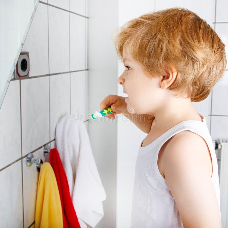 Beau garçon d'enfant en bas âge se brossant les dents, à l'intérieur image stock