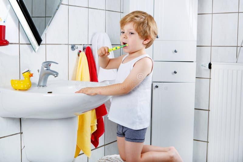 Beau garçon d'enfant en bas âge se brossant les dents, à l'intérieur images stock