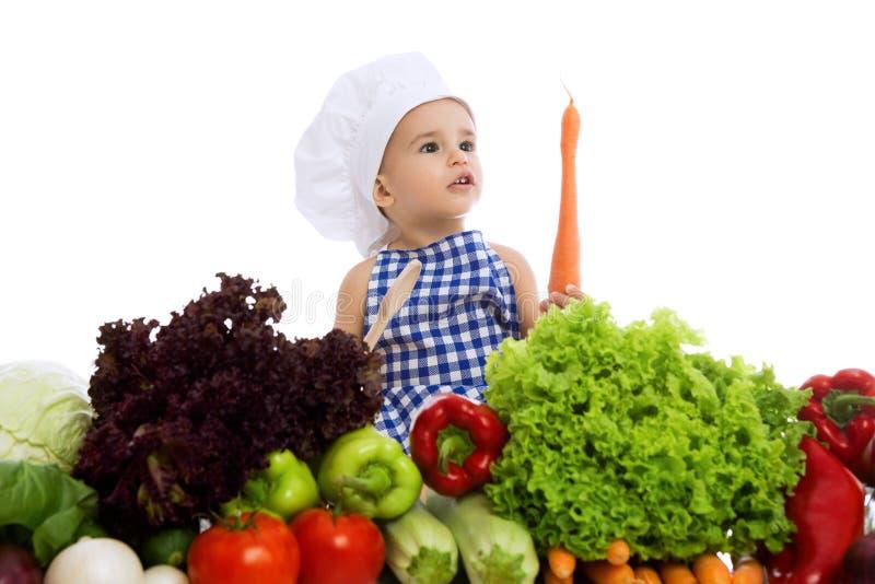 Beau garçon d'enfant utilisant un chapeau de chef avec le légume sain de nourriture images libres de droits