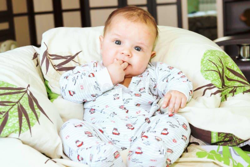 Beau garçon nouveau-né s'asseyant dans un costume photographie stock