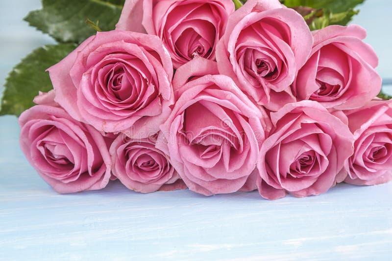 Beau grand groupe de fleurs roses roses se trouvant sur le fond clair image stock