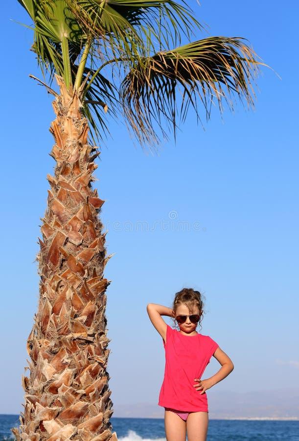 Beau gril mignon d'enfant dans des lunettes de soleil à la mode de mode presque posant photo stock