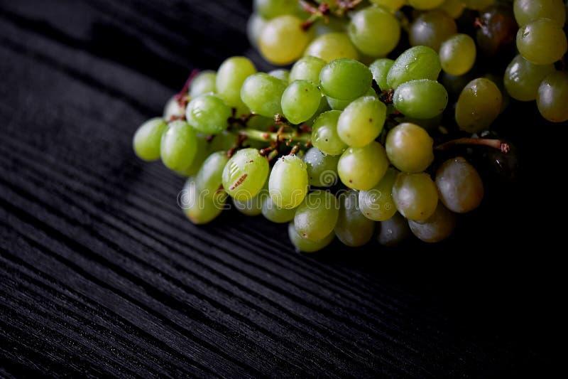 Beau groupe de raisins frais sur un fond en bois foncé Les gouttelettes de l'eau Consommation saine photographie stock libre de droits