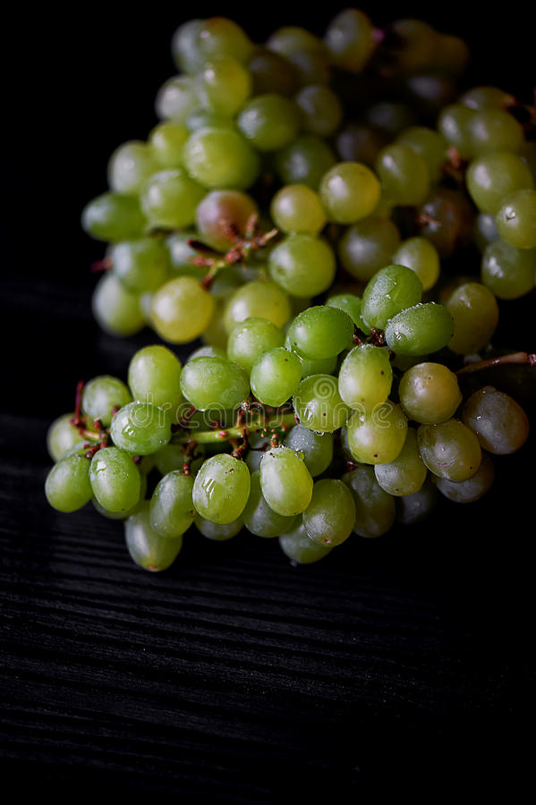 Beau groupe de raisins frais sur un fond en bois foncé Les gouttelettes de l'eau Consommation saine images stock