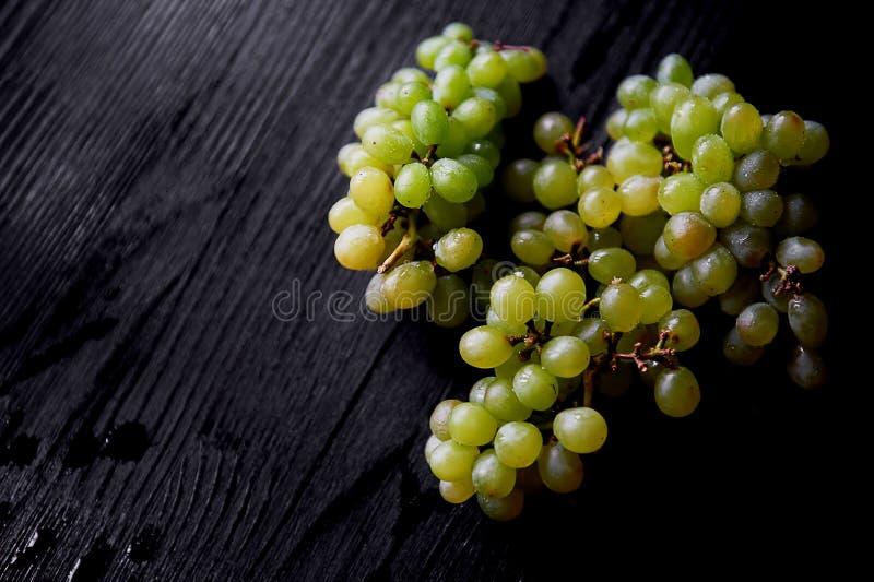 Beau groupe de raisins frais sur un fond en bois foncé Les gouttelettes de l'eau Consommation saine images libres de droits