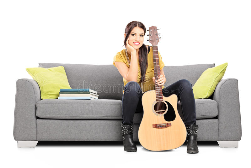 Beau guitariste féminin s'asseyant sur un sofa images libres de droits