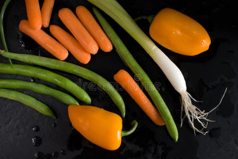 Beau jaune frais coloré et légumes verts sur un fond noir humide photographie stock libre de droits