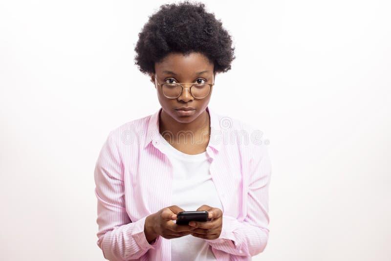 Beau jeune étudiant africain sérieux tenant le téléphone portable photographie stock