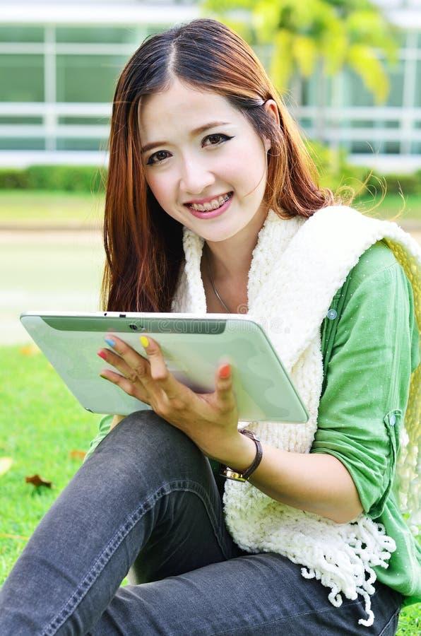 Beau jeune étudiant apprenant avec le comprimé d'ordinateur photos stock