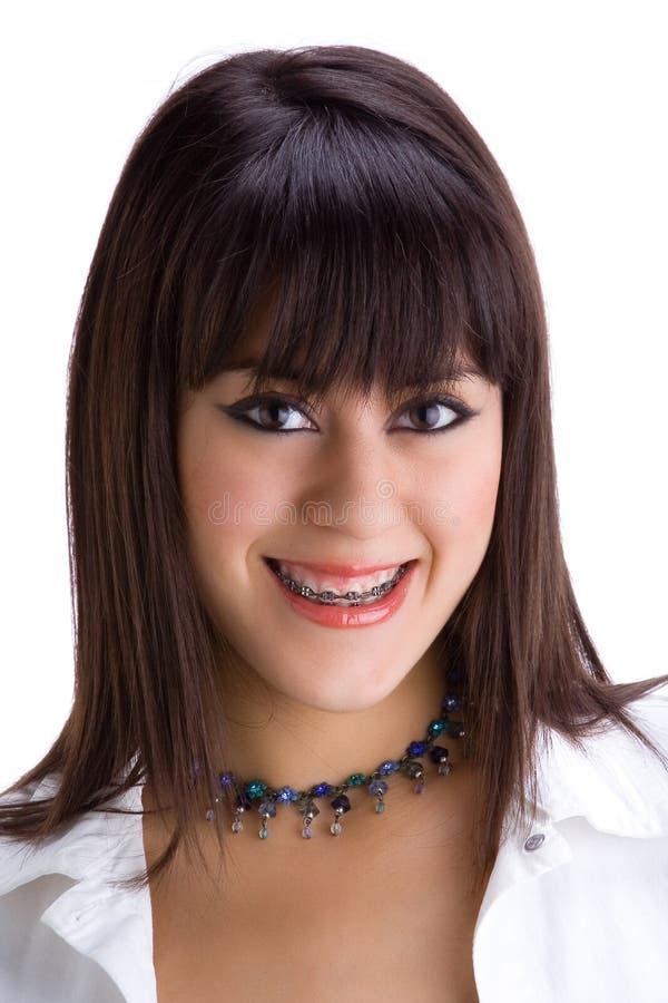 Beau jeune brunette avec des brides sur les dents 1 photographie stock