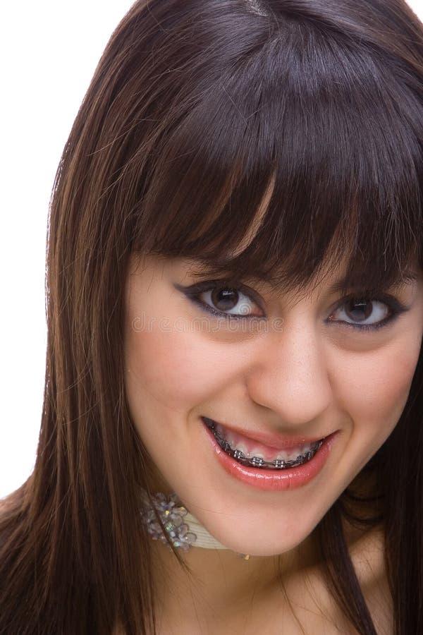Beau jeune brunette avec des brides sur les dents 2 image libre de droits