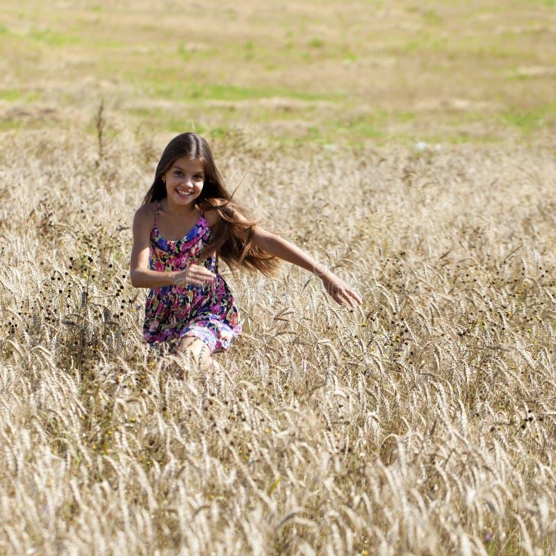 Beau jeune champ courant d'été de petite fille photographie stock libre de droits