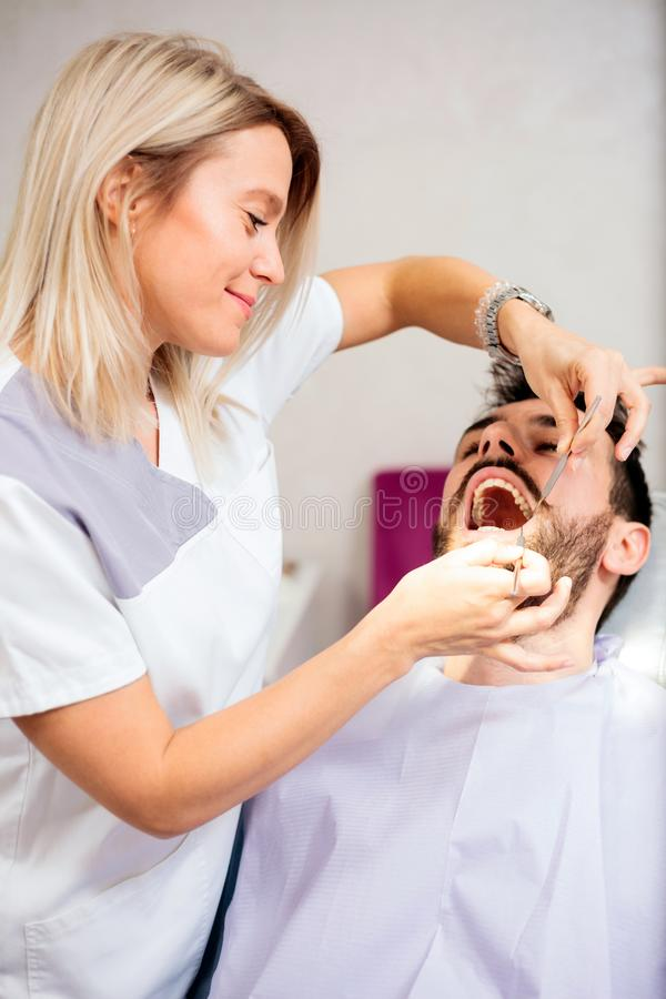 Beau jeune dentiste féminin examinant le jeune patient masculin dans la clinique dentaire image stock