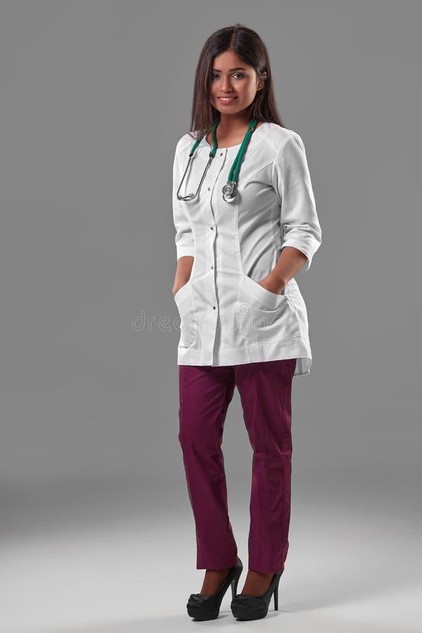 Beau jeune docteur dans une robe longue médicale avec un stéthoscope photos stock