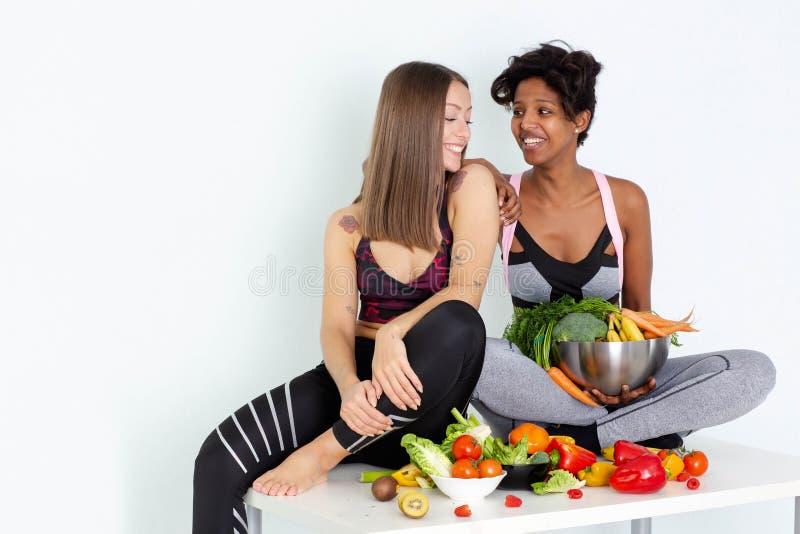Beau jeune emplacement femelle sur la table posant derrière une pile des fruits frais et des légumes d'isolement sur le fond blan photographie stock libre de droits