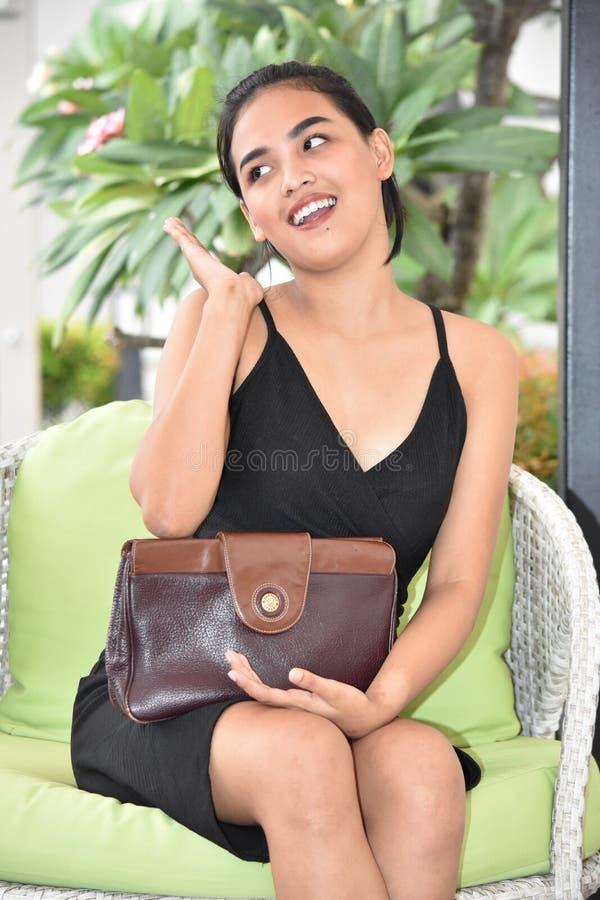 Beau jeune féminin avec la bourse tout en se reposant photo stock