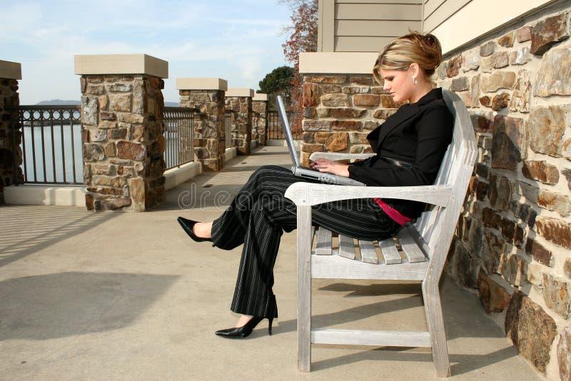 Beau jeune femme au lac avec l'ordinateur portatif photo libre de droits