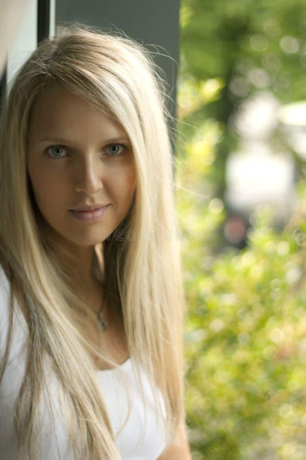 Beau jeune femme au windo photographie stock