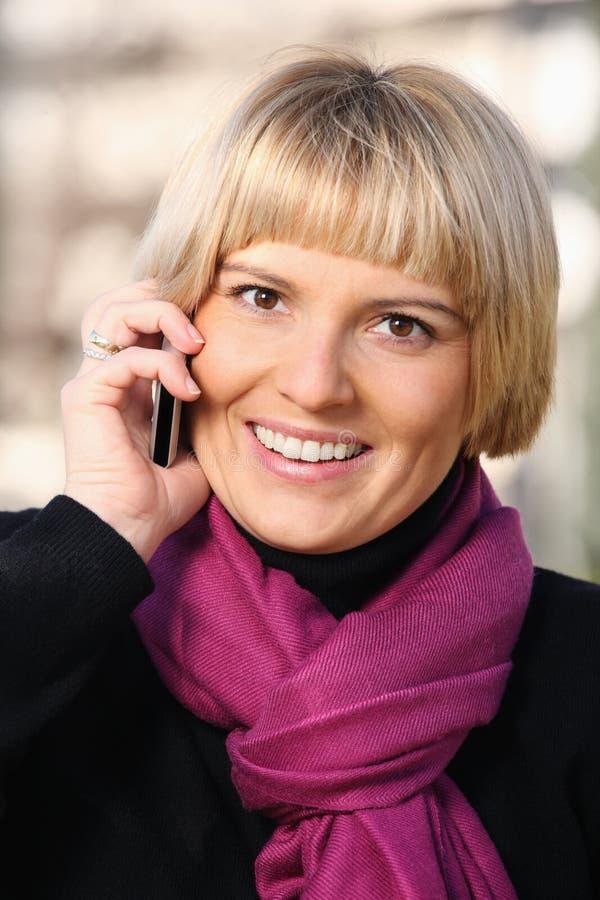 Beau jeune femme avec son téléphone portable photographie stock libre de droits