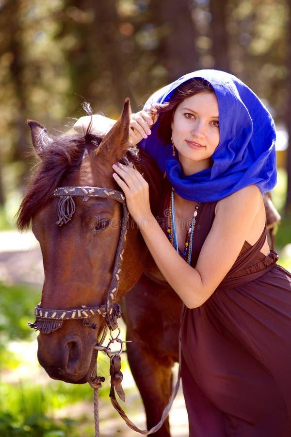 Beau jeune femme avec un cheval extérieur photographie stock libre de droits