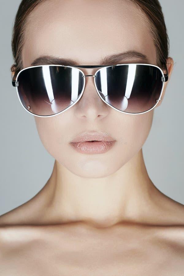 Beau jeune femme dans des lunettes de soleil photo stock